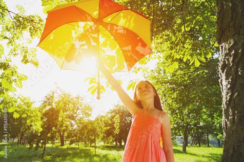 Fotografia  Happy redhead girl with umbrella in summer sun. Freedom, summer,