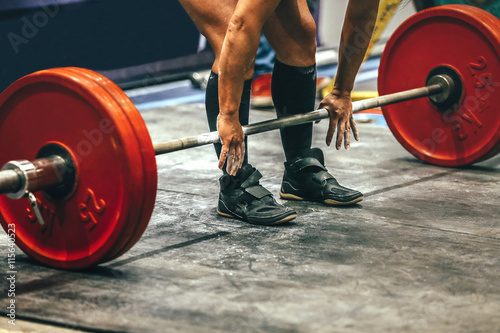 Fotografie, Obraz  male powerlifter preparing for deadlift of barbell during competition of powerli