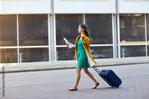 Fotografie, Obraz  happy young woman with travel bag and map in city