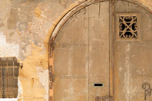 Photo  Yellow double door in yellow limestone wall