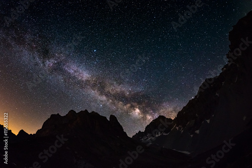 Spoed Fotobehang Nacht The outstanding beauty of the Milky Way arc and the starry sky captured at high altitude in summertime on the Italian Alps, Torino Province. Fisheye scenic distortion and 180 degree view.