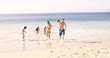 Cute family running out of the water on the beach in slow motion