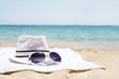 Close up of white hat and sunglasses on the beach towel as summertime concept. Beach accessories concept