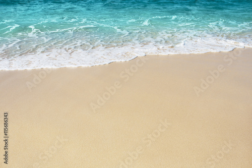 Soft wave of blue ocean on the sandy beach, background.