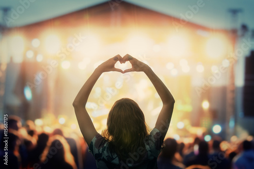 Obraz Girl making a heart-shape symbol for her favorite band. - fototapety do salonu