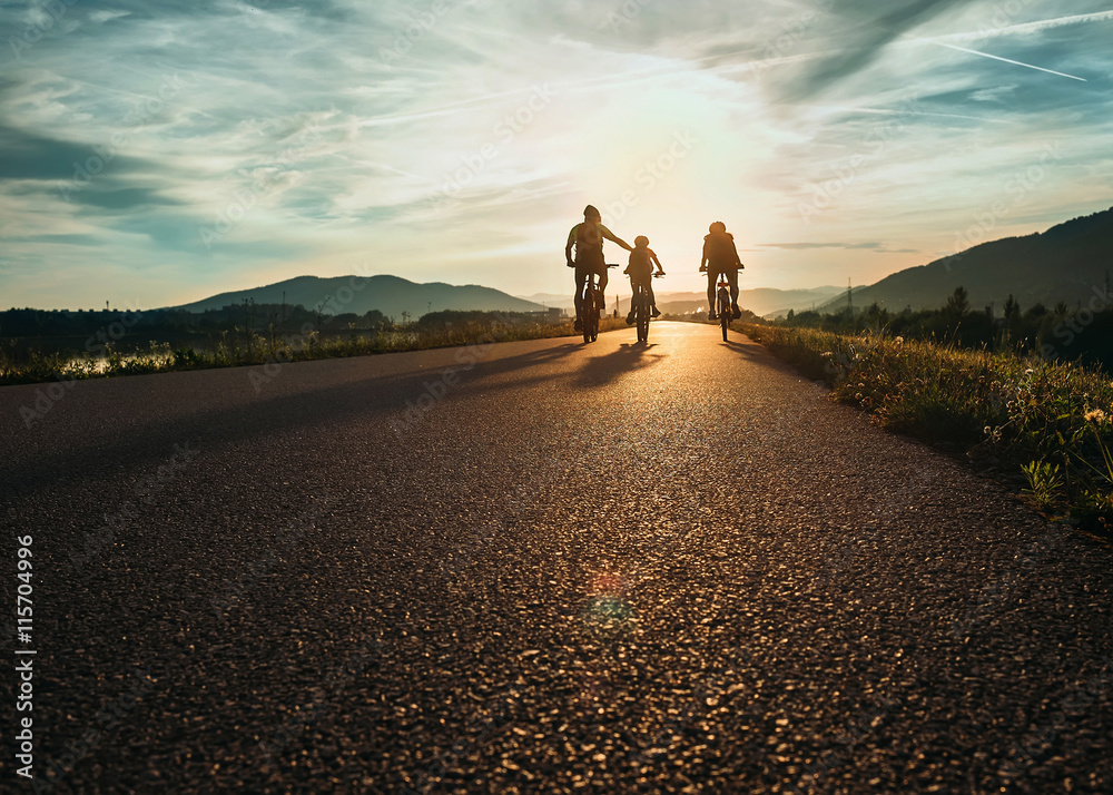 Fototapety, obrazy: Cyclists family traveling on the road at sunset
