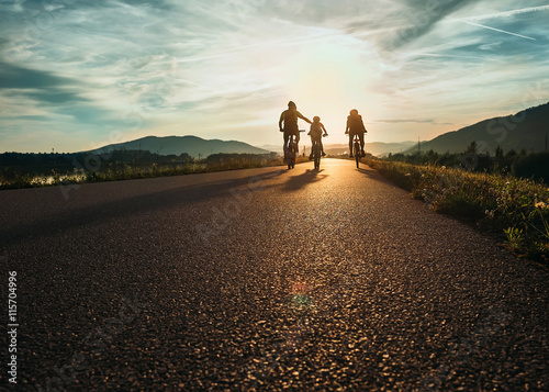 Obraz Cyclists family traveling on the road at sunset - fototapety do salonu