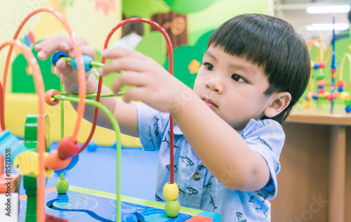 Photo  Asian boy is playing with educational toy