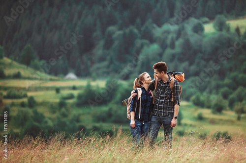 фотография A couple hikers Hiking with backpacks walk along a beautiful mountain area