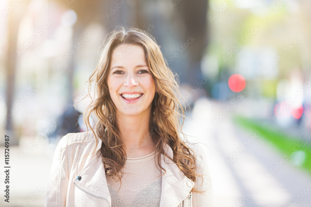 Fototapety, obrazy: Portrait of a beautiful young woman in Hamburg. She is caucasian, on her early twenties, brunette with long hair. Looking at camera and smiling. Smart casual clothes, blurred urban background