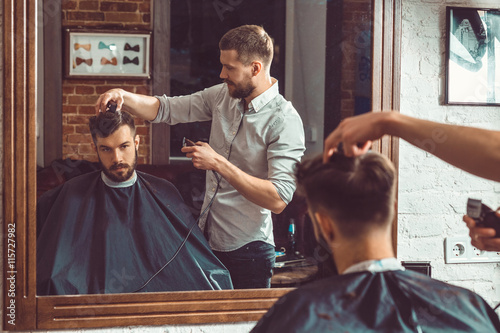 mata magnetyczna Young handsome barber making haircut of attractive man in barbershop