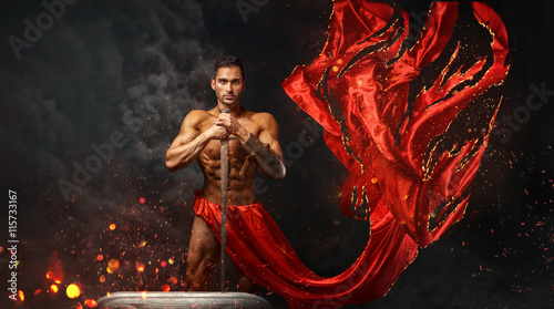 Fényképezés  Artistic portrait of muscular male in red waving fabric.