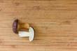 ein Pilz liegt in zwei Teile geschnitten auf einem Holzbrett