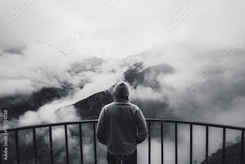 View from behind of a man standing at view point looking to beautiful landscape with foggy mountains in the distance Poster