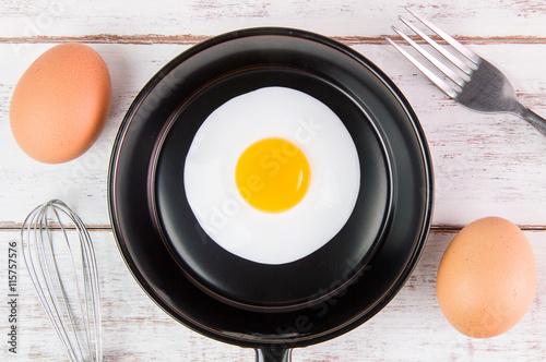 Deurstickers Gebakken Eieren Fried egg in small pan with handle on blue wooden board