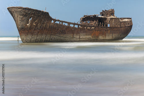Foto op Plexiglas Schipbreuk Rusty boat aground on the coast of Morocco