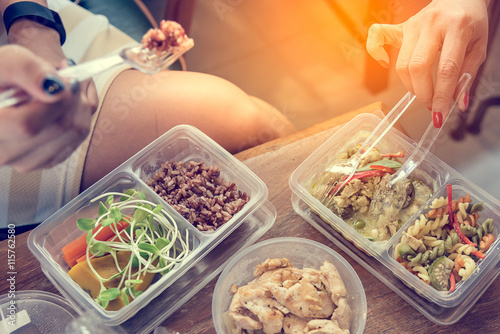 Women eating Healthy food in lunch box on wooden table.