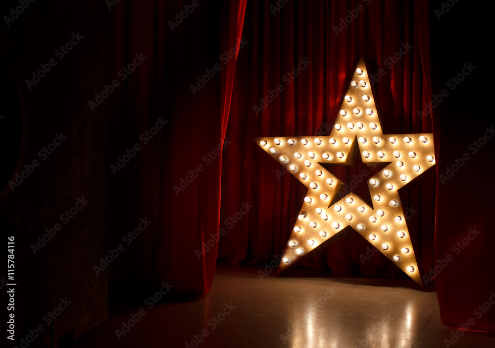 Photo  Photo of golden star with light bulbs on red velvet curtain on stage