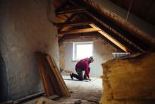 Mid Adult Man Marking On Floor In Attic Under Renovation