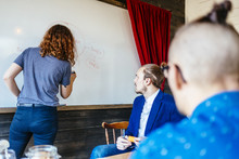 Businesswoman Writing On Whiteboard Leading Meeting In Board Room