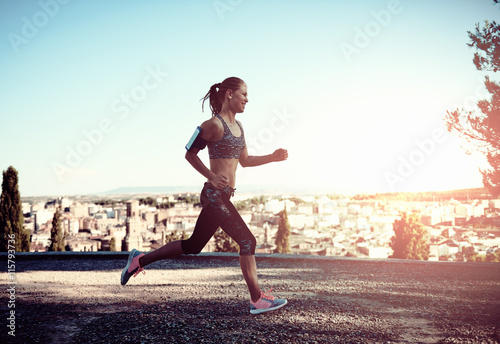 Smiling female jogger training in the morning sunny day. Active woman with athletic body running in the countryside.
