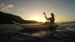 SLOW MOTION: Young woman kayaking on ocean at golden sunset