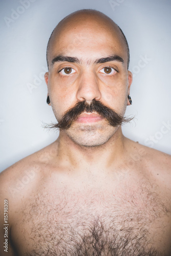 Fotografie, Obraz  Studio portrait of young mid adult man with mustache looking at camera - beard c