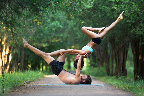 Foto  Acro yoga, two sporty people practice yoga in pair, couple doing stretching exer