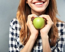 Beautiful Girl With Green Apple On Grey Background