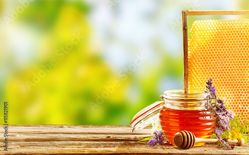Jar of fresh honey with flowers and honeycomb Fototapeta