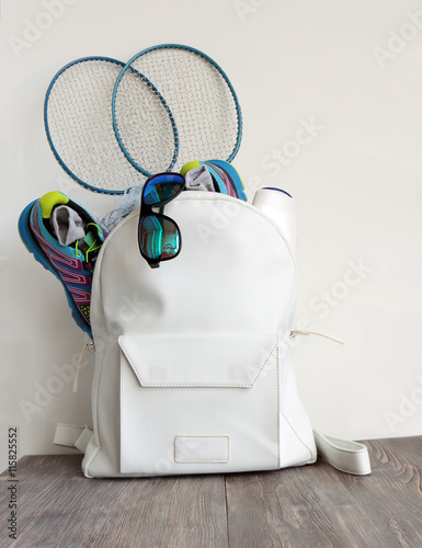 Fotografie, Obraz  White leather bag (daypack) with sport shoes, sunglasses and badminton battledor