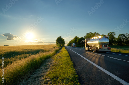 Trucks with chrome tank driving on asphalt road along the corn field at sunset Fototapete