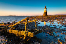 Plover Scar Lighthouse At Cockerham On Morecambe Bay In The UK. The Lighthouse Has Been Damaged By The Sea - The Ladder In The Foreground Was Once Part Of The Structure. At Sunset.