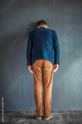 Photo Rear view of stressed man punching the wall