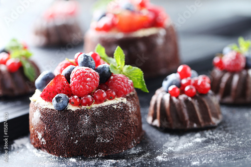 Deurstickers Dessert Sweet chocolate cakes with berries on black wooden table