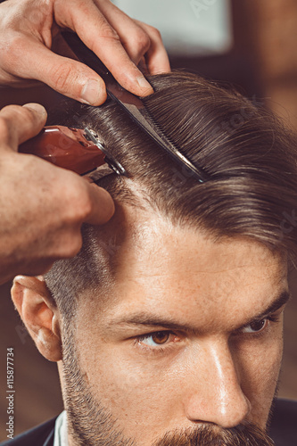 The hands of young barber making haircut to attractive man in barbershop Fototapeta