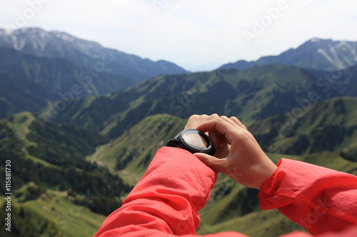 young woman hiker checking the altimeter on sports watch at mountain peak Wallpaper Mural