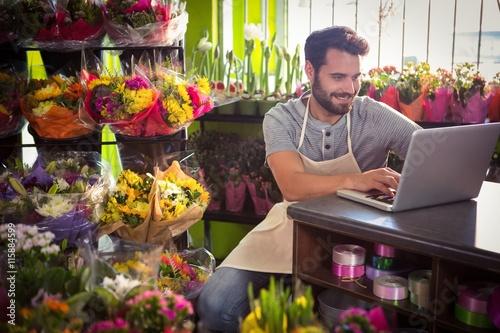 Male florist using laptop