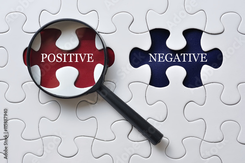 Photo Magnifying Glass On Missing Puzzle with POSITIVE/NEGATIVE Word, Antonym Concep