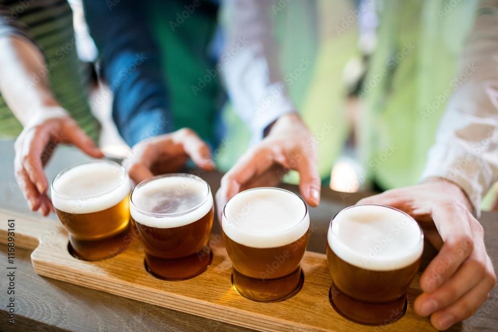Foto  Friends reaching towards beer sampler on counter