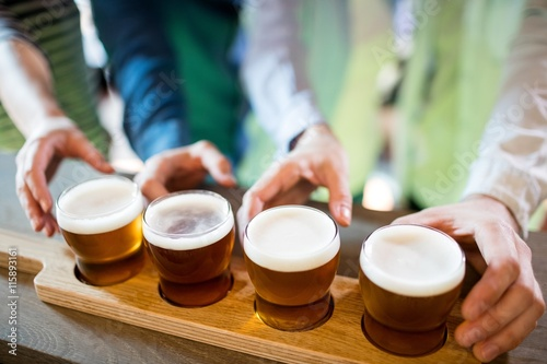 Photo Friends reaching towards beer sampler on counter