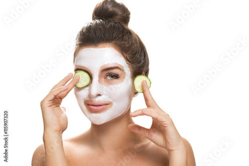 Fotografía  Woman with facial mask and cucumber slices in her hands