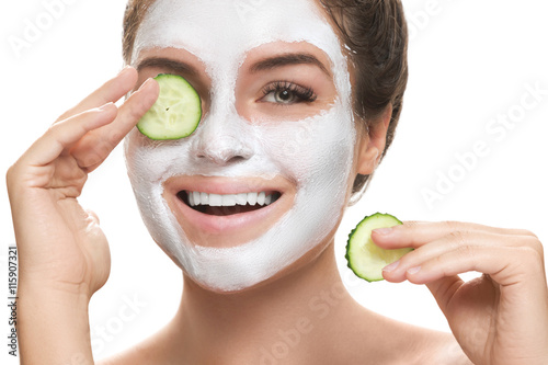 Fotografiet Woman with facial mask and cucumber slices in her hands