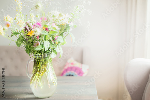 Lovely Wild Flowers Bunch In Glass Vase On Table In Light Living