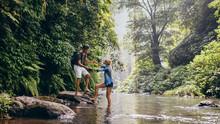 Man Helping Woman Crossing Stream