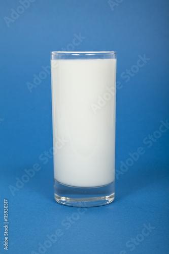 Glas Milch vor blauem Hintergrund