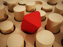 Red Prism Wooden Block Standing Out Among Wooden Cylinders. 3D Illustration
