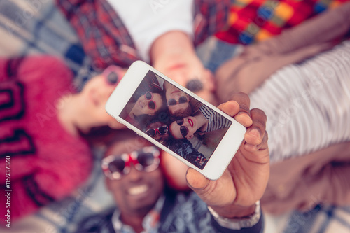 Fotografía  Picture of best friends making selfies on mobile or smart phone while spending free time on picnic in parklane