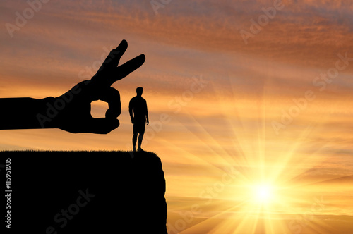 Canvas Print Silhouette hand wants to push a man off a cliff