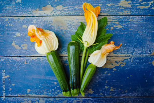 Flowering and ripe zucchini on blue wooden background